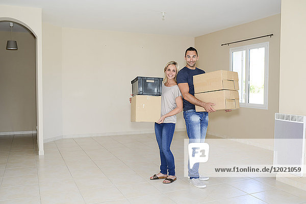 Happy young couple carrying cardboard boxes and moving into their new house.