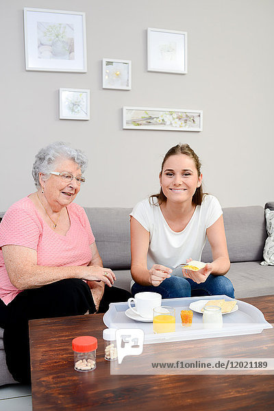 Cheerful young girl serving breakfast to elderly woman at home.
