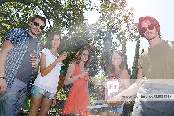 Groupe of happy and cheerful young people having fun around barbecue grill during summer holiday party outdoor in the garden. Groupe of happy and cheerful young people having fun around barbecue grill during summer holiday party outdoor in the garden.