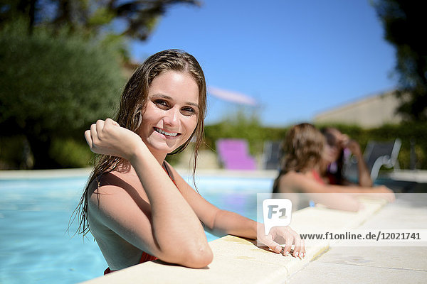 Portrait of a beautiful young woman in the poolside of a resort swimming pool during summer holiday.