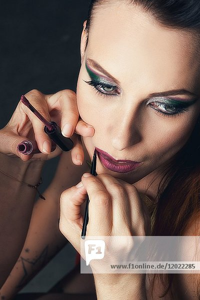 Portrait of a young woman doing makeup lips