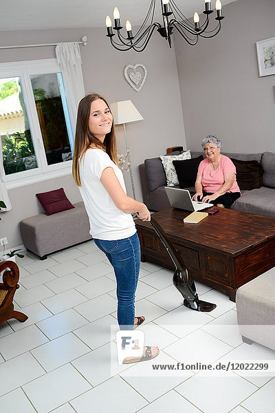 Cheerful young girl helping with household chores elderly woman at home.