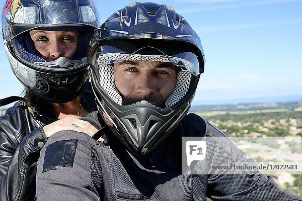 Happy young biker couple riding motorbike in summer.