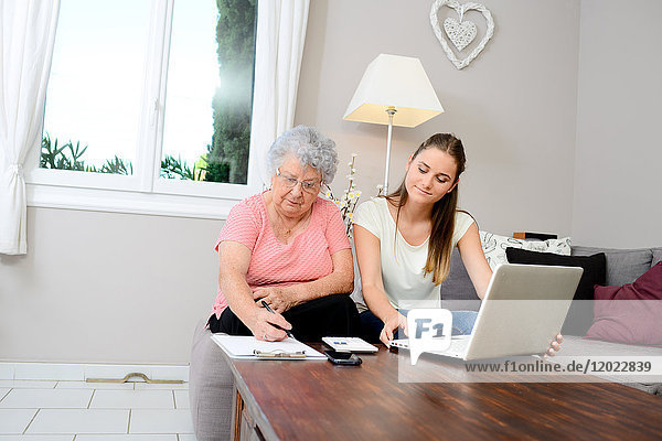 Cheerful young woman helping old person doing paperwork and telephone call.