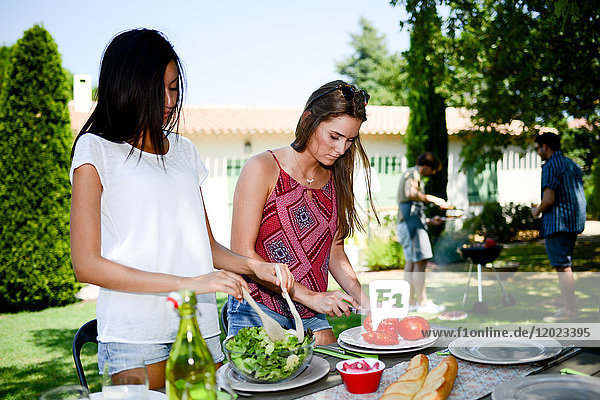 Two beautiful young woman in the garden preparing tomato salad for barbecue party during summer holiday. Two beautiful young woman in the garden preparing tomato salad for barbecue party during summer holiday.