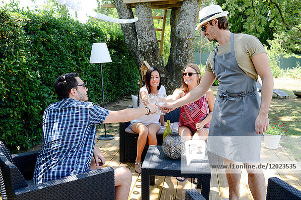 Group of young and cheerful people having a toast in a garden party outdoor in the backyard during summer holiday. Group of young and cheerful people having a toast in a garden party outdoor in the backyard during summer holiday.
