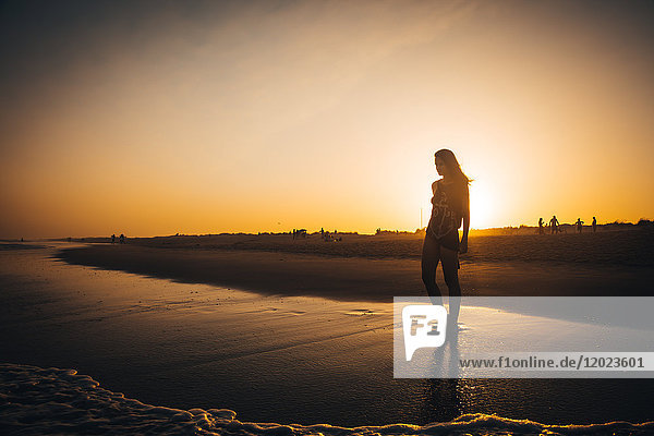 Young woman walking on the beach Praia do Barril in a sunset  deTavira city  region of Algarve  Portugal