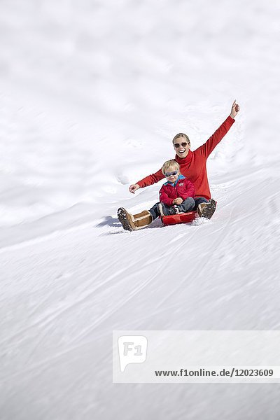 Portrait of smiling woman sitting with her childs on sled in snow  Crans-Montana  Swiss Alps  Switzerland