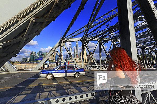 Asia  China  Shanghai. Photographer and taxi on Waibaidu bridge