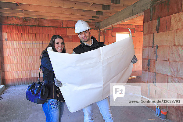 France  young architect and customer in a house in construction.