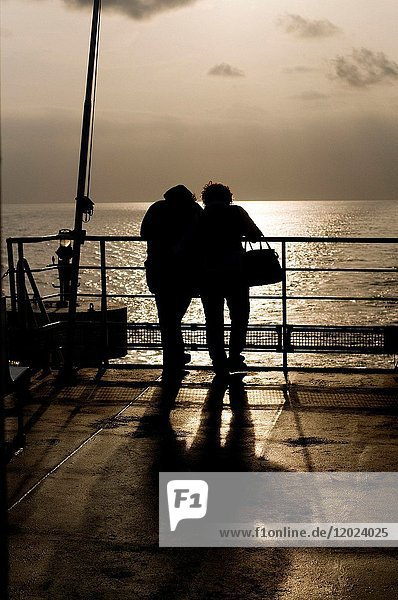 Silhouettes of two people on ship's deck  looking at view