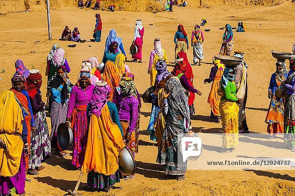 Rajasthani women in bright colors working (carrying dirt) at a construction project along the Jaipur-Agra Road  India.
