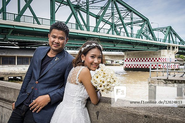 Just married,  in background Memorial Bridge,  Bangkok,  Thailand.