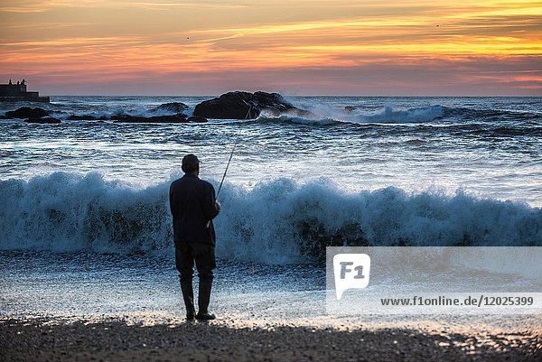 Man fishing from the beach of Atlantic Ocean in Foz do Douro district of Porto city  second largest city in Portugal.