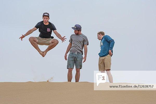 Junger Mann springt auf Sanddüne  zwei schauen zu  Namibia  Afrika