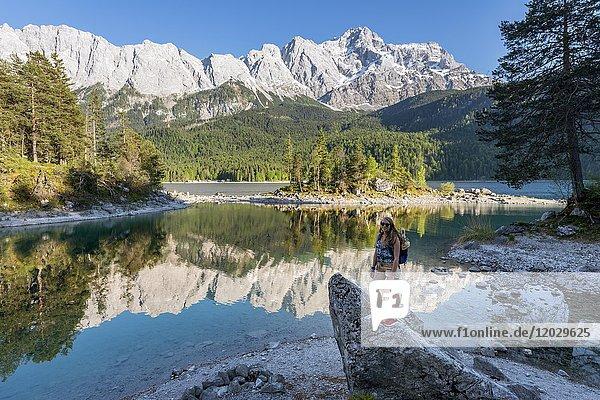 Wanderin steht auf Felsen und blickt in die Kamera  Eibsee und Zugspitze  Wettersteingebirge  bei Grainau  Oberbayern  Bayern  Deutschland  Europa