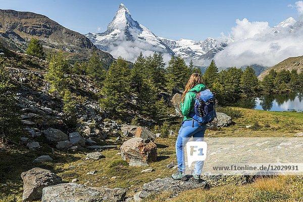 Wanderin steht auf Felsen und blickt in die Ferne  hinten Grindijsee und schneebedecktes Matterhorn  Wallis  Schweiz  Europa