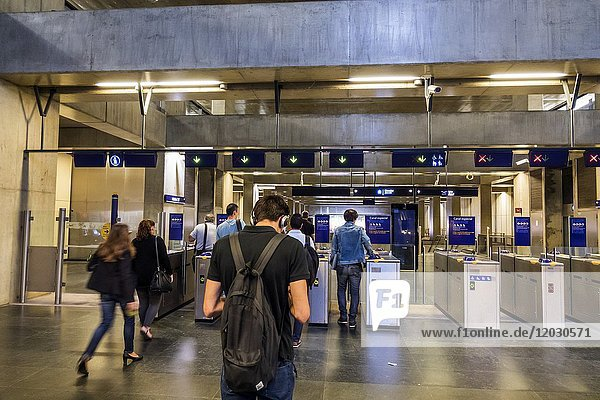 Portugal  Lisbon  Metro Lisboa  public transportation  mass transit  subway  Terreiro do Paco  station  turnstile  baffle gate  man  woman  commuter  riders  commuters  inside