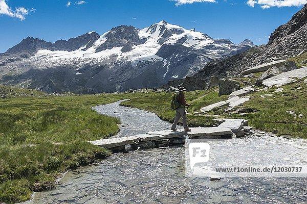 Wanderin überquert Bergbach  Almwiese Valle delle Meyes  2700 m ü. NHN  Rundwaderweg von Pont  hinten Panorama des Grand Paradiso  Valsavarenche-Tal  Gran Paradiso  Alpen  Autonome Region Aostatal  Italien  Europa