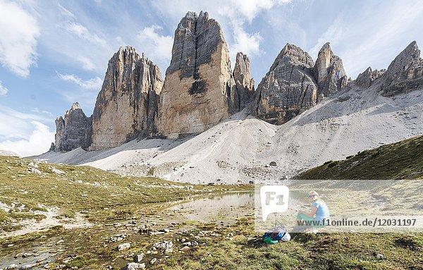 Wanderin macht Pause  Nordwände der Drei Zinnen  See bei Col Forcellina  Sextner Dolomiten  Provinz Südtirol  Trentino-Südtirol  Alto-Adige  Italien  Europa