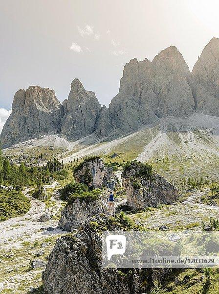 Wanderer steht auf Felsen  Geröllfeld unterhalb der Geislerspitzen  hinten die Geislergruppe  Villnösstal Sass Rigais  Dolomiten  Südtirol  Italien  Europa