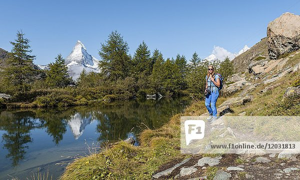 Hiking on the 5-lake hiking trail  snow-covered Matterhorn reflected in the lake  Grindijsee  Valais  Switzerland  Europe