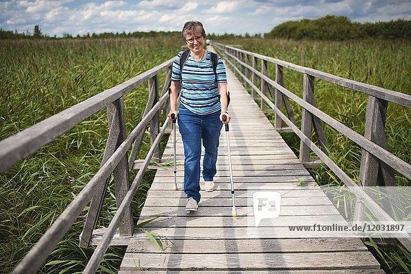 Ältere Frau läuft an Krücken auf Federseesteg  Naturschutzgebiet Federsee  UNESCO Weltkulturerbe  Bad Buchau  Oberschwaben Baden-Württemberg  Deutschland  Europa