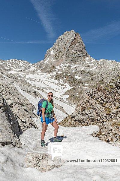 Wanderin auf dem Wanderweg zum Königssee und der Wasseralm  Steinernes Meer mit Schnee im Frühling  hinten Grießkogel  Nationalpark Berchtesgaden  Bayern  Deutschland  Europa