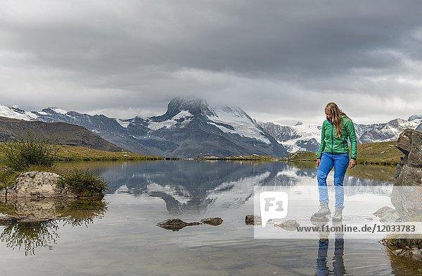 Wanderin geht über Steine im Wasser  Stellisee  wolkenverhangenes Matterhorn  Wallis  Schweiz  Europa