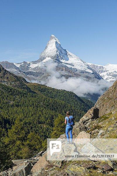 Wanderin steht auf Felsen und blickt in die Ferne  hinten schneebedecktes Matterhorn  Wallis  Schweiz  Europa