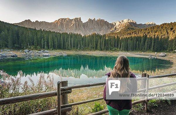Frau blickt auf Karersee  Lago di Carezza  Morgenstimmung  Latemargruppe spiegelt sich im See  Berggipfel Diamantidturm  Östliche Latemarspitze  Col Coron  Welschnofen  Bozen  Südtirol  Italien  Europa