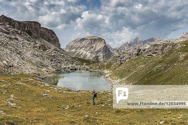 Wanderin am Bergsee Lech de Crespeina  hinten Col de La Pieres  Naturpark Puez-Geisler  Dolomiten  Selva di Val Gardena  Südtirol  Trentino-Alto Adige  Italien  Europa