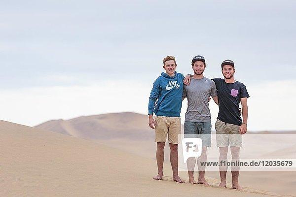 Drei junge Männer auf Sanddüne  Namibwüste  Namibia  Afrika