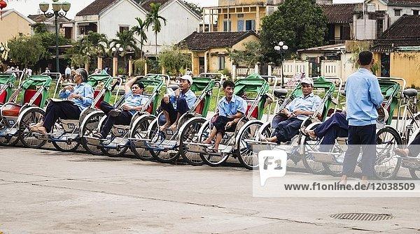 Rickshaw riders sit in their bicycle rickshaws at the roadside  Hoi An  Vietnam  Asia