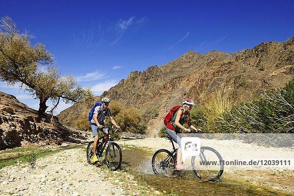 Touristen mit Mountainbikes in der Gegend von Feynan Ecolodge  Jordanien  Asien