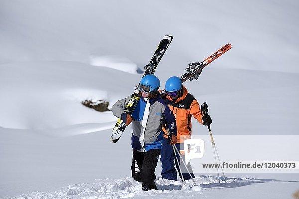 Skifahrer stapfen mit geschulterten Skiern im Schnee  Freerider  Hochfügen  Zillertal  Tirol  Österreich  Europa