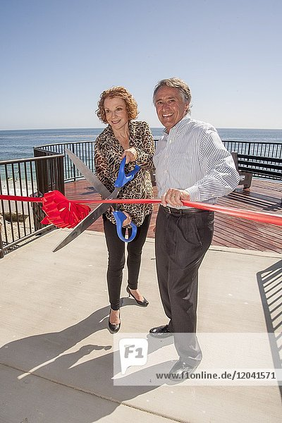 Local politicians use a giant pair of scissors to cut a ribbon at opening ceremonies for a new beach access staircase in Laguna Beach  CA.