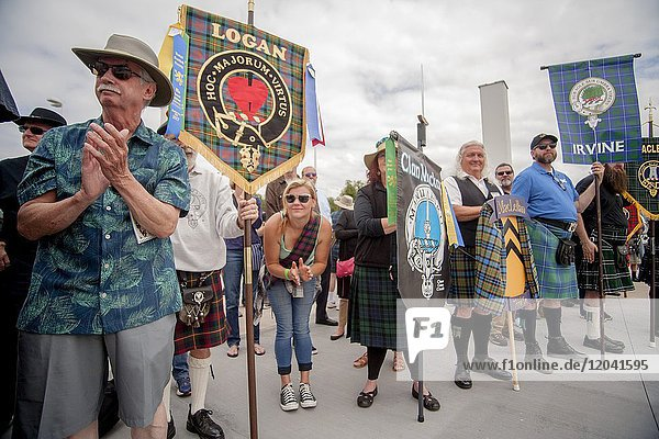 Banners of different Scottish clans are on display at an ethnic festival in Costa Mesa  CA  as a young woman applauds.
