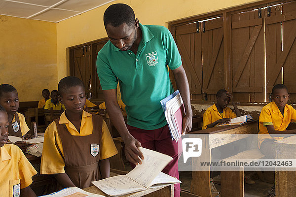 A male teacher teaching a classroom of children at a primary school in Ghana  West Africa  Africa