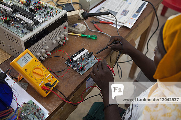 A woman  known as a Solar Mama  fixes a solar circuit board  Tanzania  East Africa  Africa