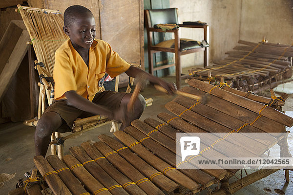 A school boy playing music on a large wooden xylophone at his primary school in Ghana  Africa