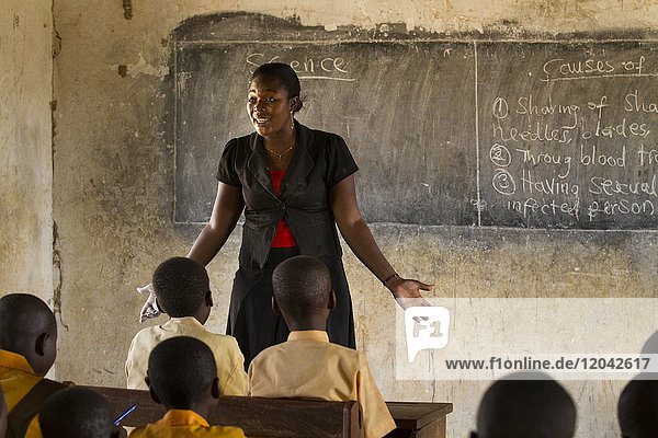 A female teacher teaching science to a classroom of students at a primary school  Ghana  West Africa  Africa