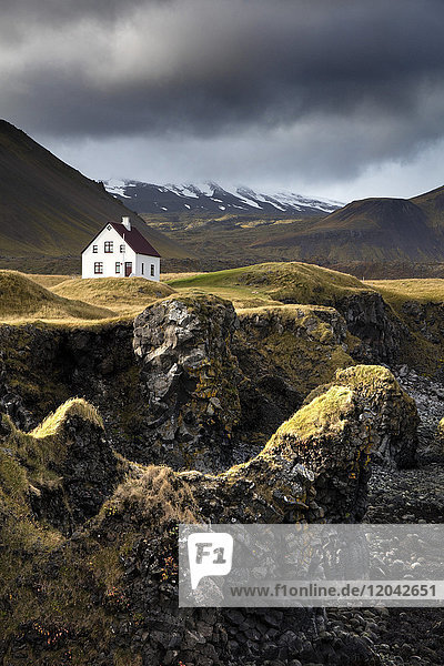 Lone house and sea stacks in stormy weather  Arnastapi  Snaefellsnes Peninsula  Iceland  Polar Regions