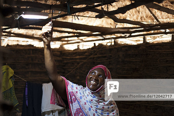 A woman smiling as she turns on the new solar light in her mud hut  Tanzania  East Africa  Africa