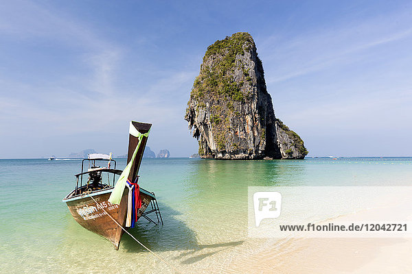 Traditional Longtail boat moored by Phra Nanag Beach with limestone islands in the background  Krabi  Thailand  Southeast Asia  Asia