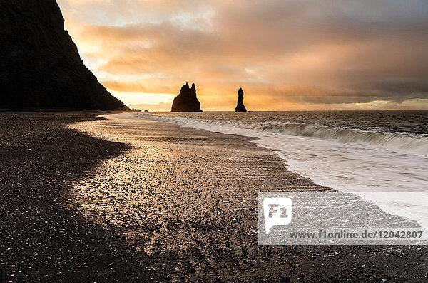 Rock stacks of Reynisdrangar at sunrise  from Halsanefs Hellir Beach near Vik  South Iceland  Polar Regions