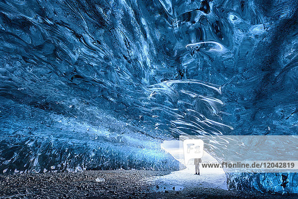 View from inside ice cave under the Vatnajokull Glacier with person for scale  near Jokulsarlon Lagoon  South Iceland  Polar Regions