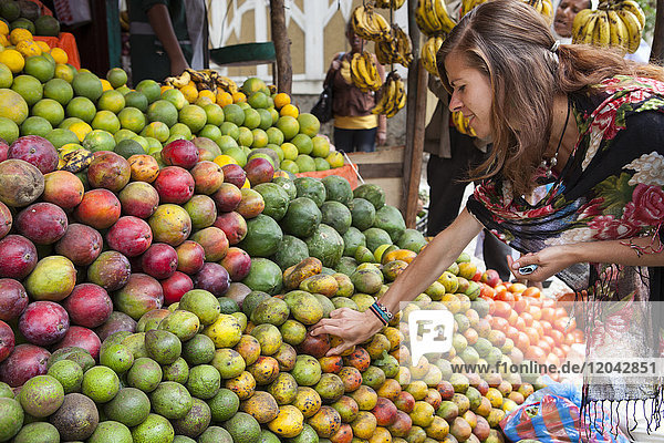 A VSO volunteer buying fresh fruit from a fruit stall on the side of the road in Addis Ababa  Ethiopia  Africa