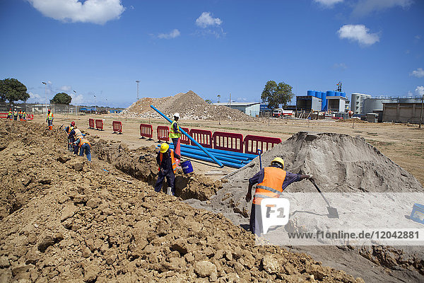 Workmen dig a trench and install a new pipeline  Mtwara  Tanzania  East Africa  Africa