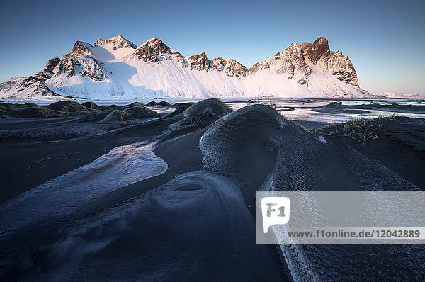 Frozen winter landscape at dusk with Vestrahorn mountains in distance  Stokksnes  South Iceland  Polar Regions